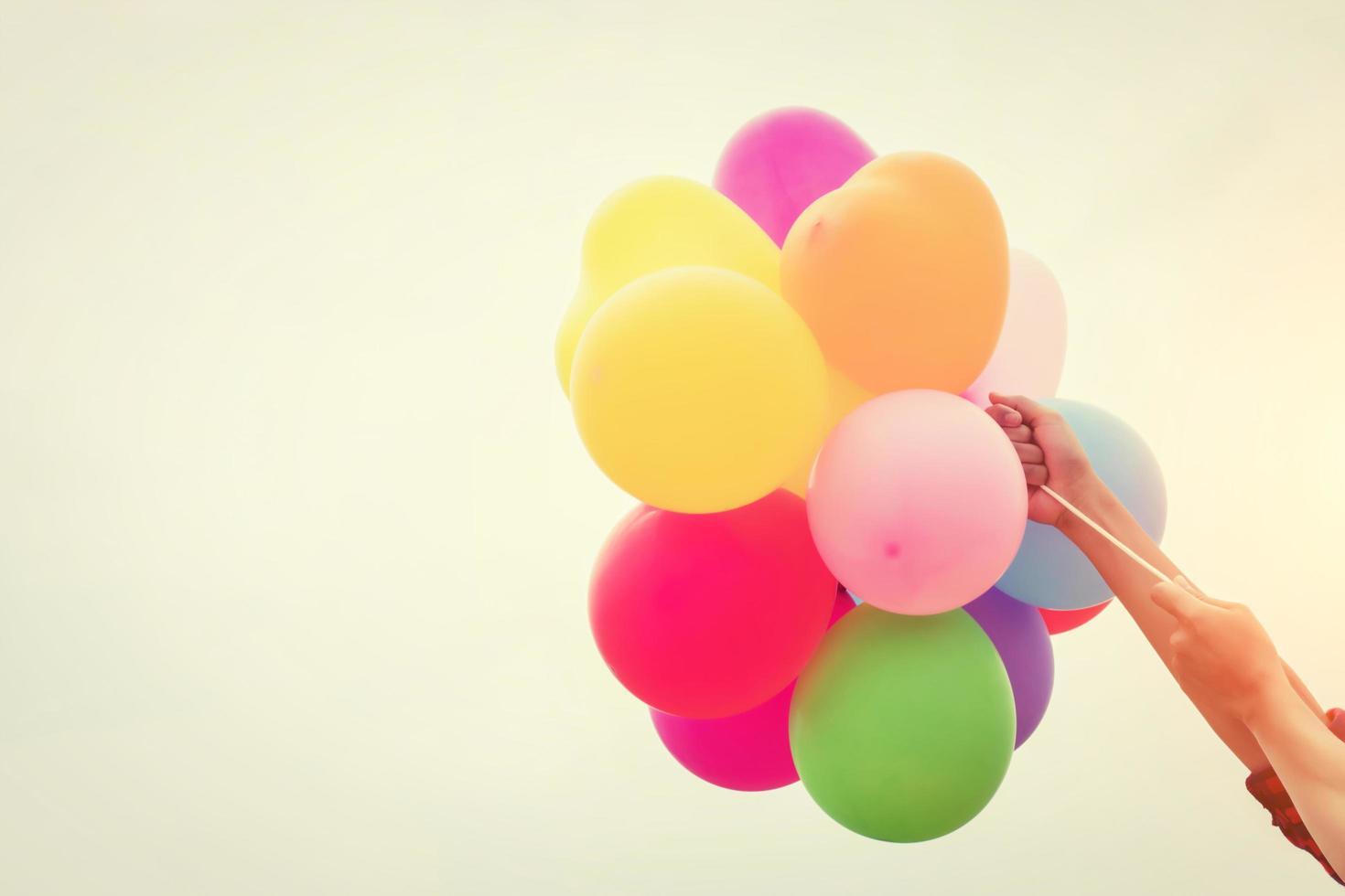 manos sosteniendo globos de colores bajo el sol del verano foto