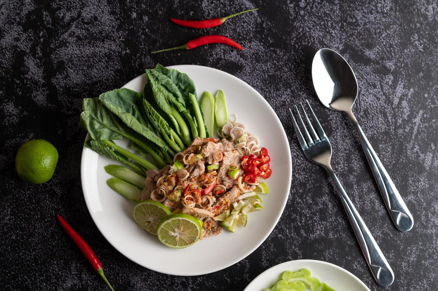 Spicy lime pork salad on a bed of greens photo