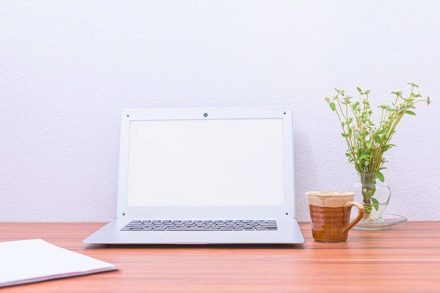 computadora portátil, taza y flor en el escritorio foto