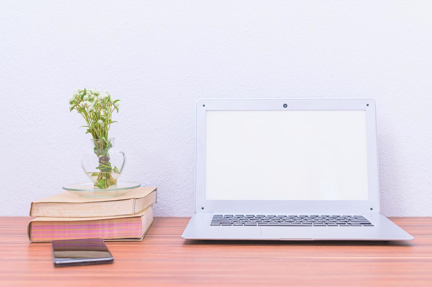 computadora portátil y libros en el escritorio foto