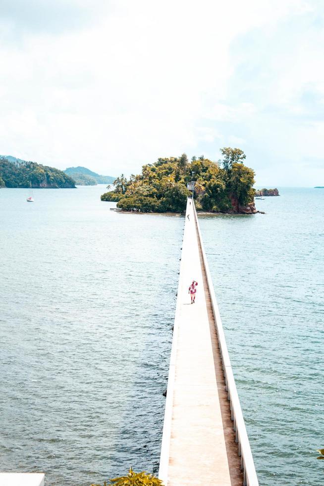 persona caminando sobre un puente a una isla foto