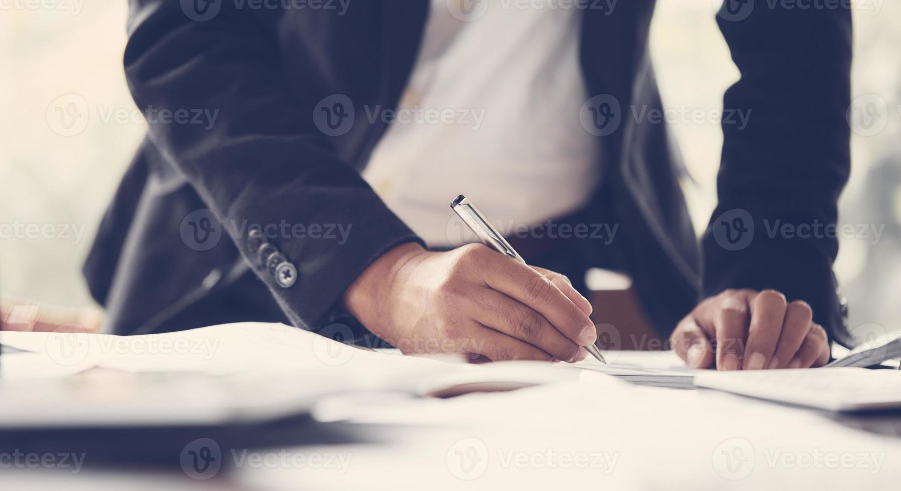 hombre escribiendo en una hoja de papel foto
