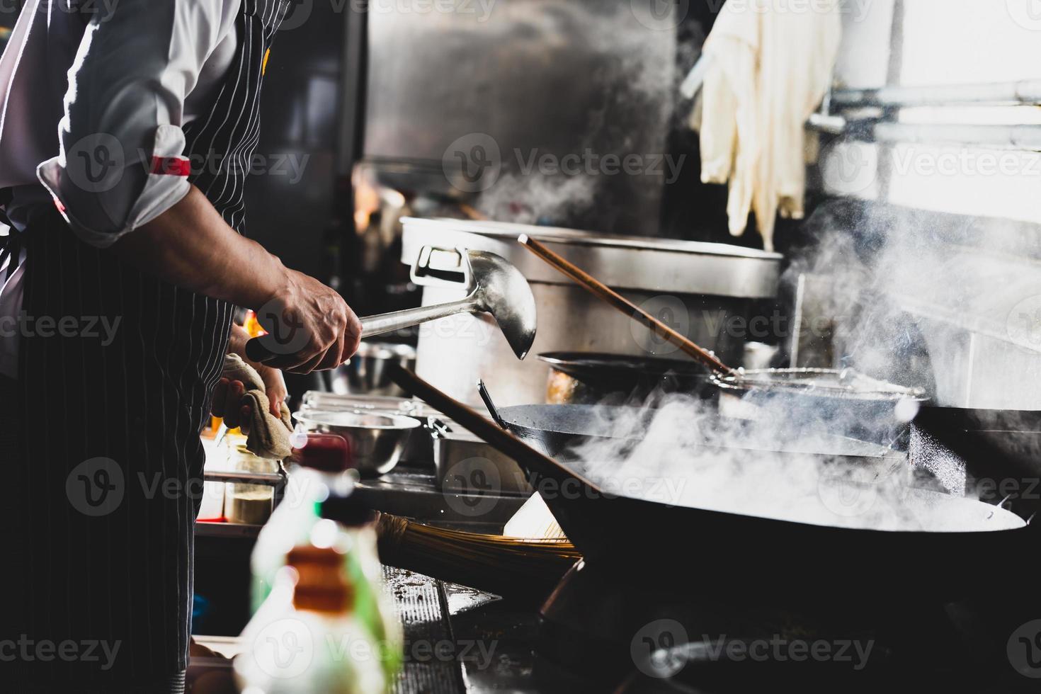 chef haciendo un salteado en un wok foto