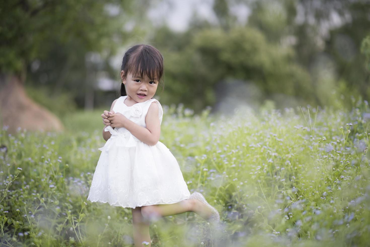 Happy little girl standing in the meadow in a white dress photo