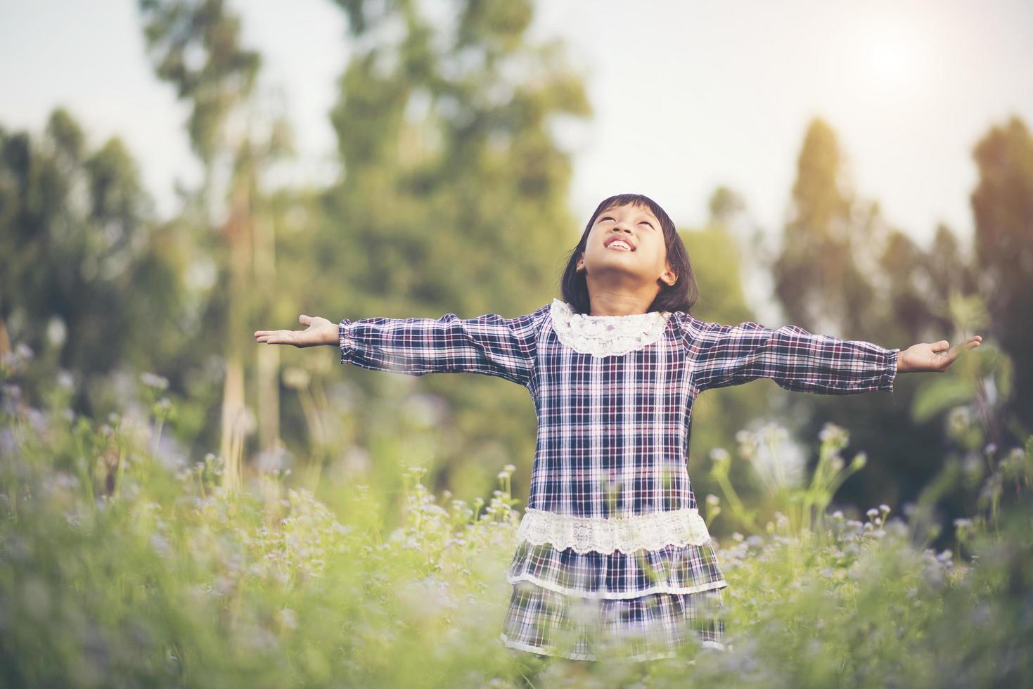 Little girl raising her hands in the fresh air photo