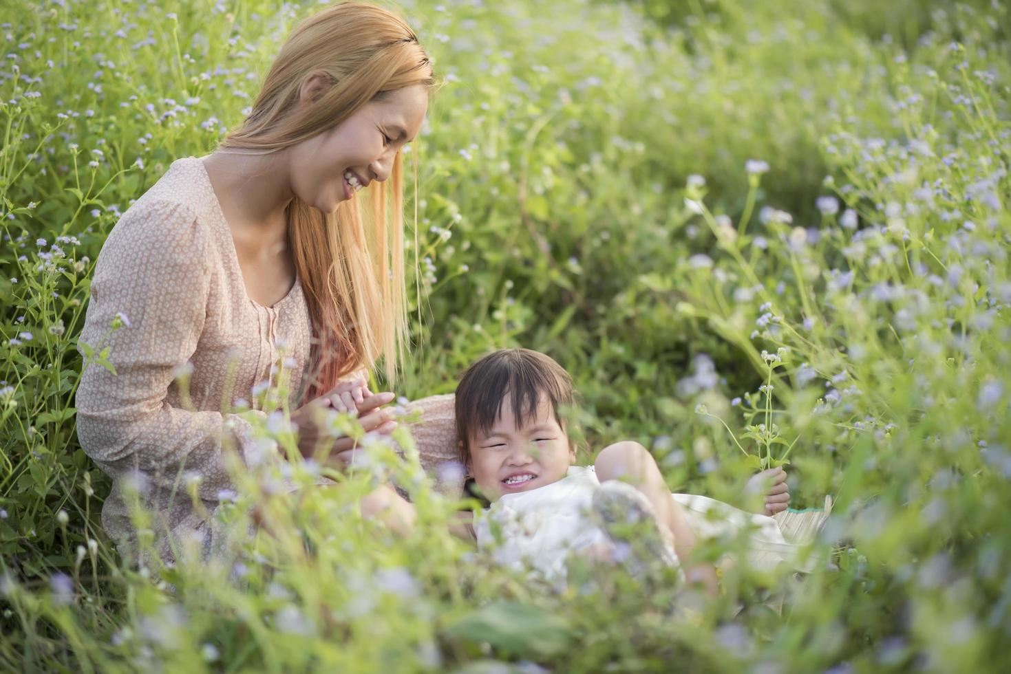 Mother and little daughter playing together in a grassy meadow photo