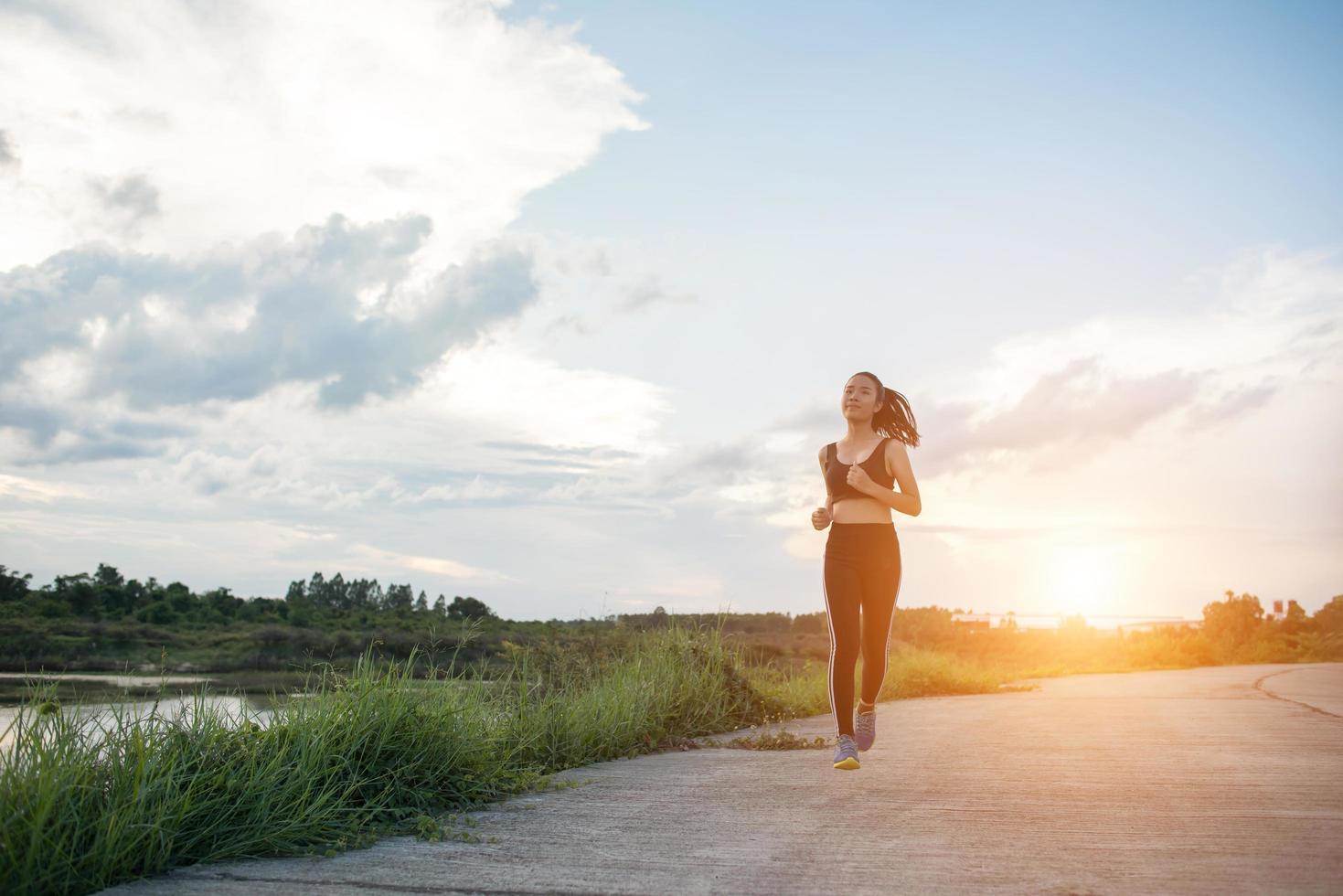 Una joven corredora feliz trotar al aire libre foto