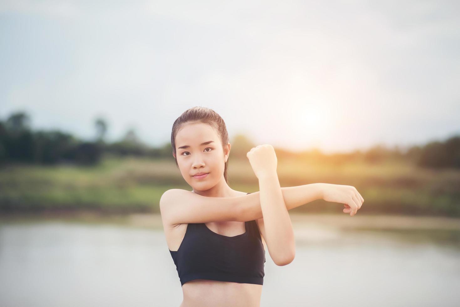 Mujer joven sana calentando al aire libre para entrenar foto