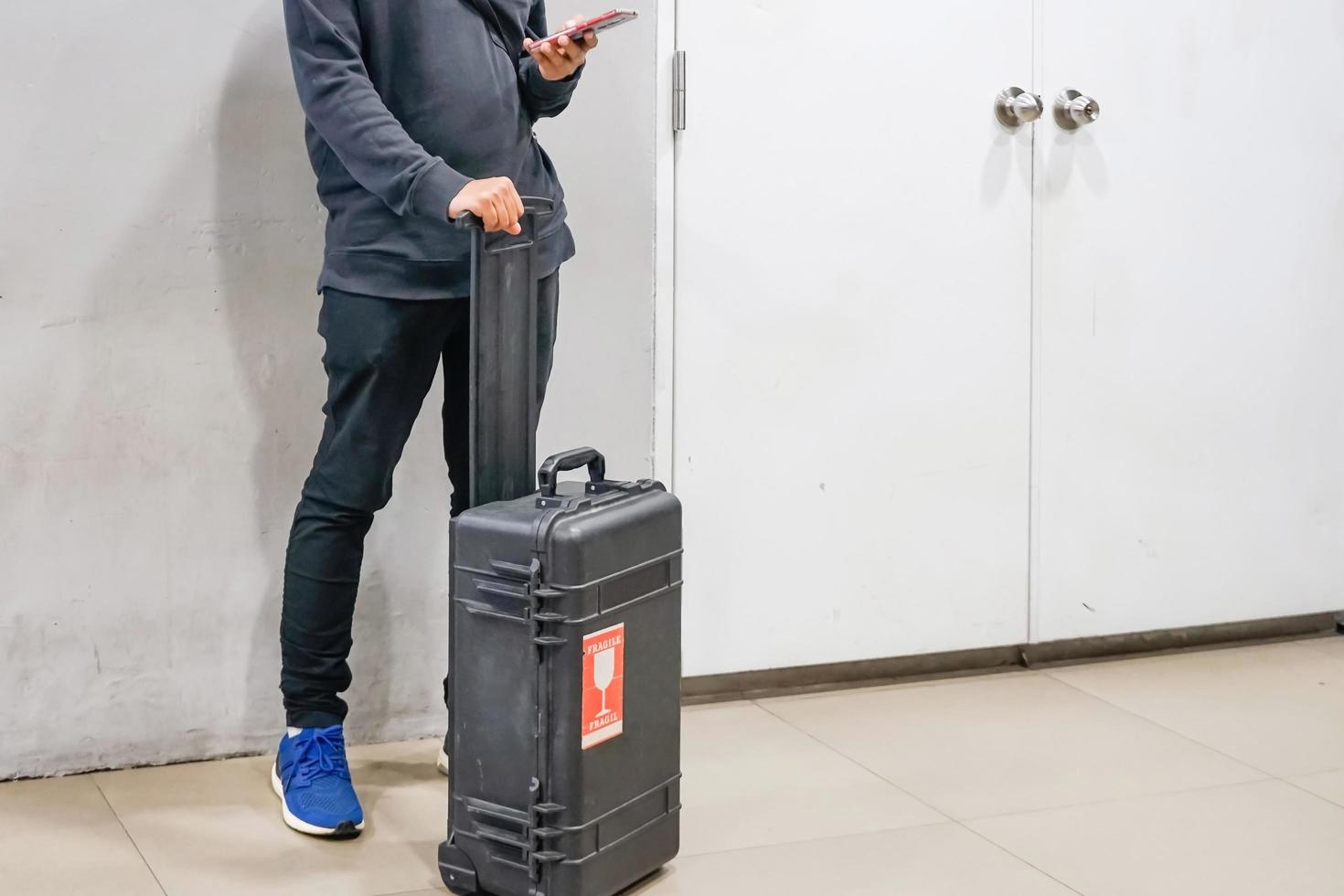Young asian man using smartphones with his luggage to flight checking at airports, travel abroad concept photo