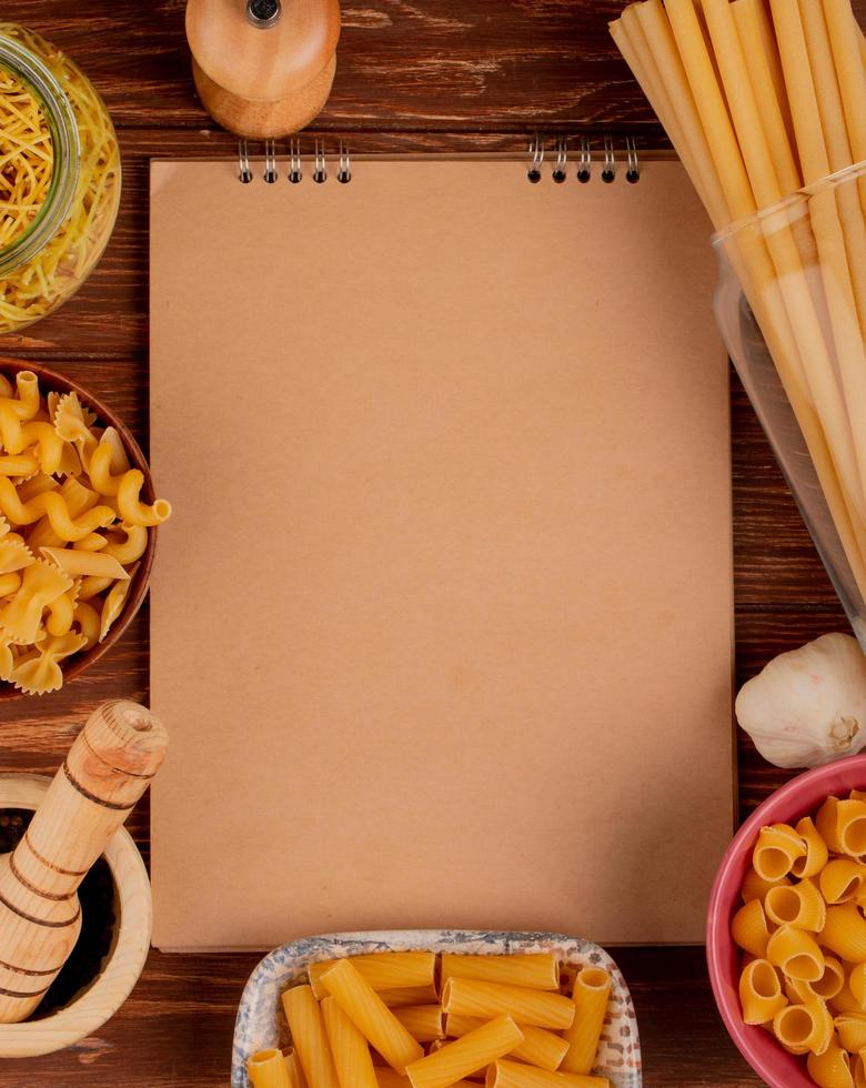 top view of different types of macaronis in bowls with salt black pepper and garlic with note pad on wooden background with copy space photo