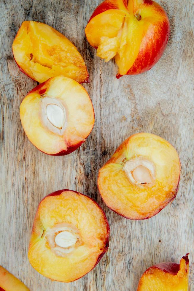 top view of cut peaches on wooden background photo