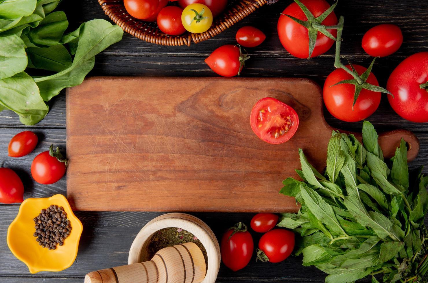 Vista superior de verduras como tomate y hojas de menta verde con semillas de pimienta negra y trituradora de ajo y tomate cortado en una tabla de cortar sobre fondo de madera foto