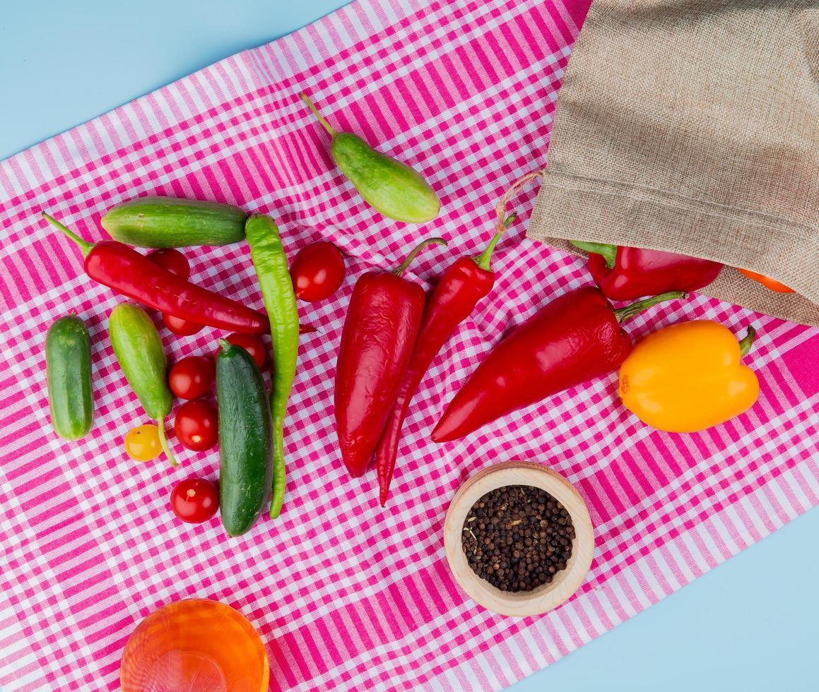 Vista superior de los pimientos que se derraman fuera del saco con pepinos, tomates y semillas de pimienta negra con aceite derretido sobre tela escocesa y fondo azul. foto