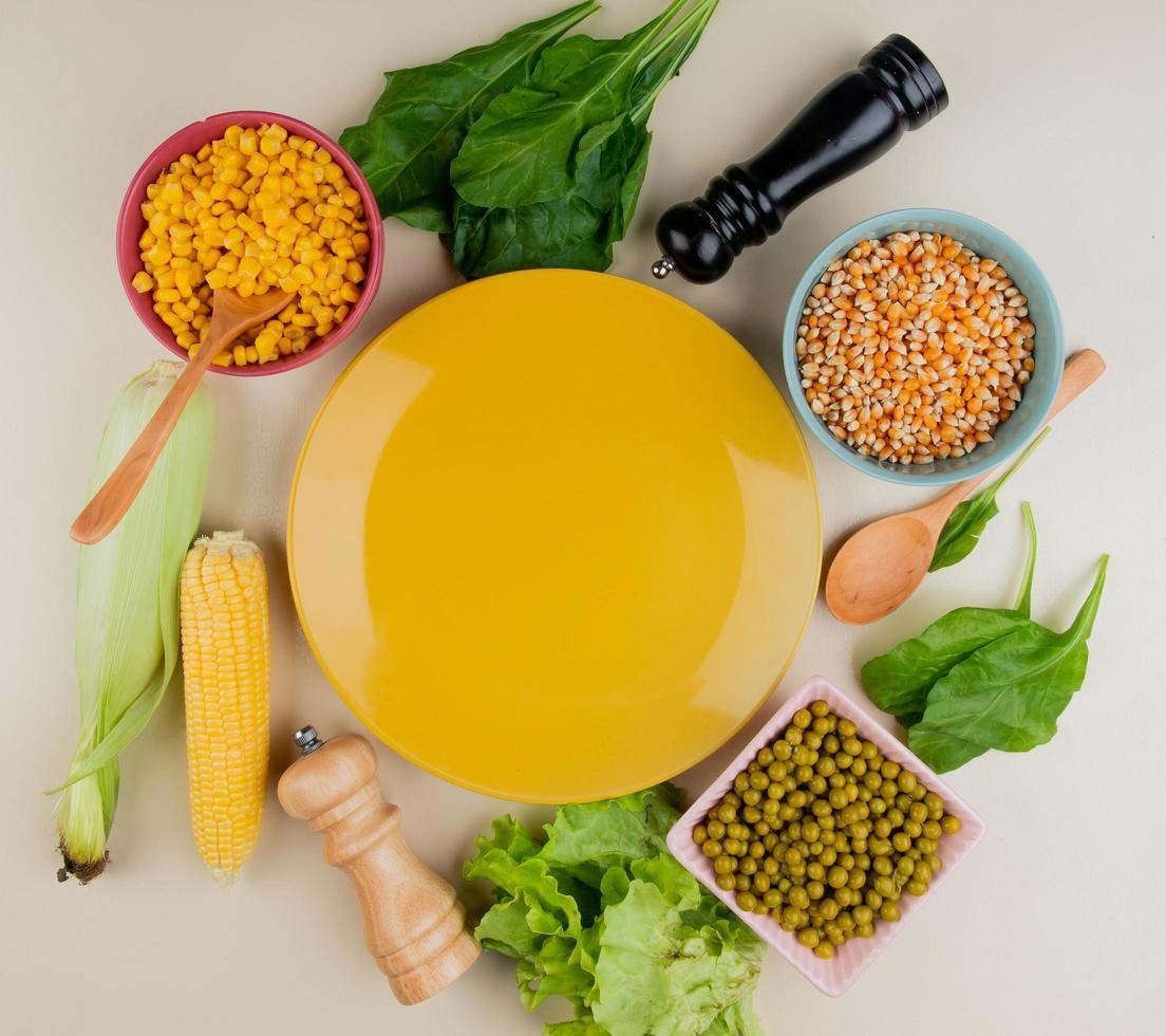 Vista superior del plato vacío con semillas de maíz cocidas y secas mazorca de maíz con cáscara espinacas lechuga guisantes verdes y cuchara de madera alrededor sobre fondo blanco. foto