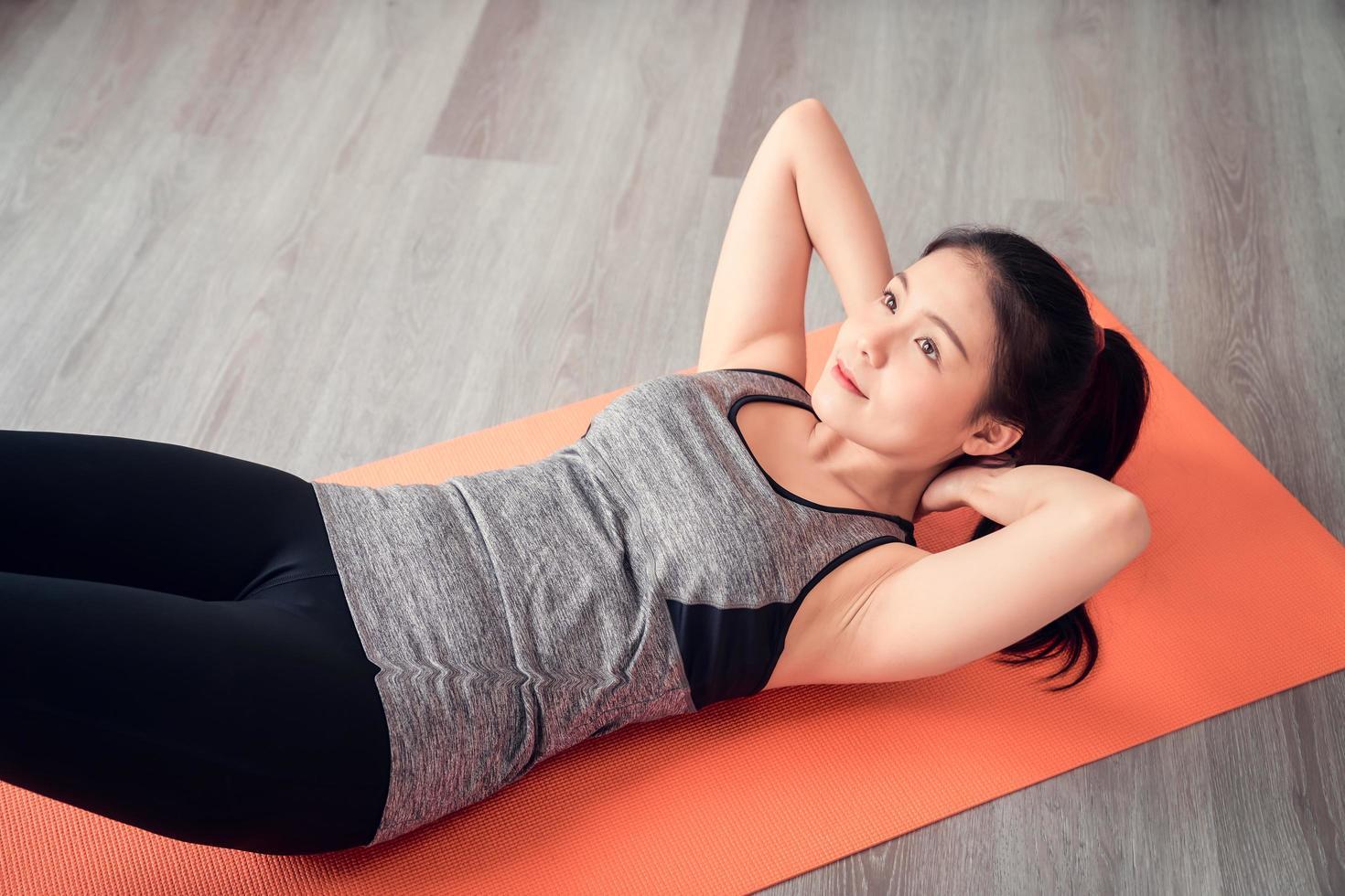 Woman sit-up on orange mat photo