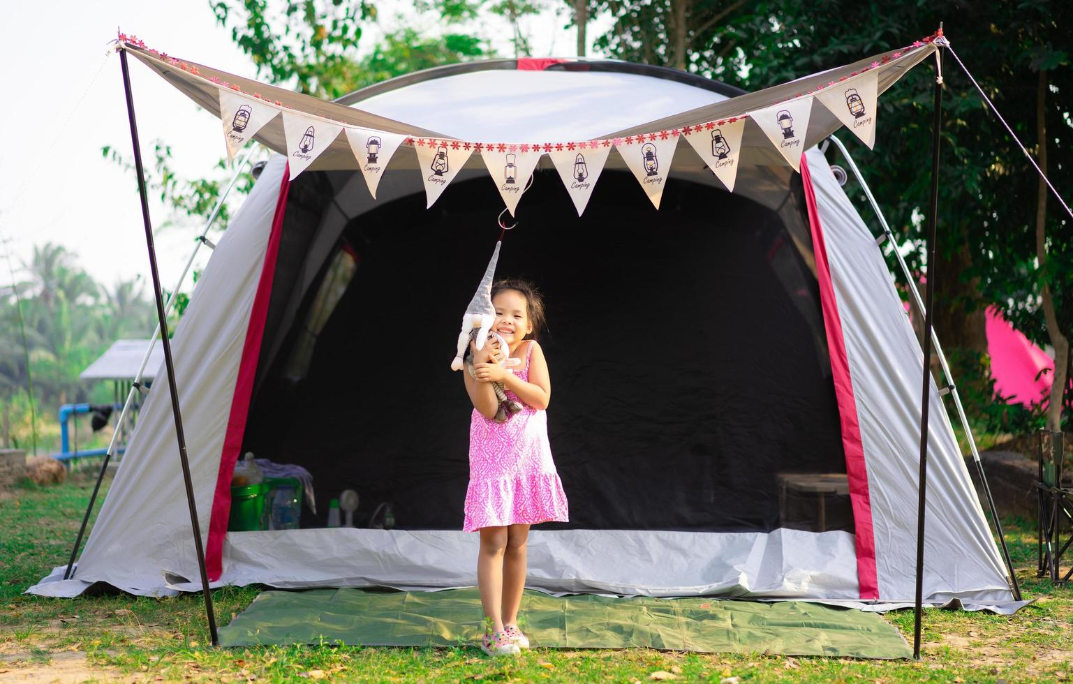 Little Asian girl standing in front of tent while going camping photo