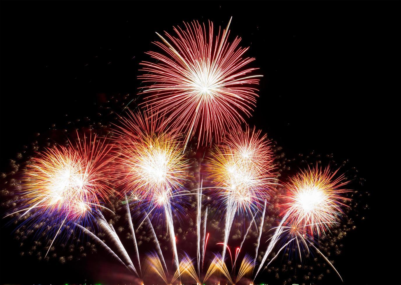 Fondo de fuegos artificiales de vacaciones coloridos abstractos celebración en la víspera de año nuevo un festival de exhibición de fuegos artificiales de alegría en el cielo nocturno foto