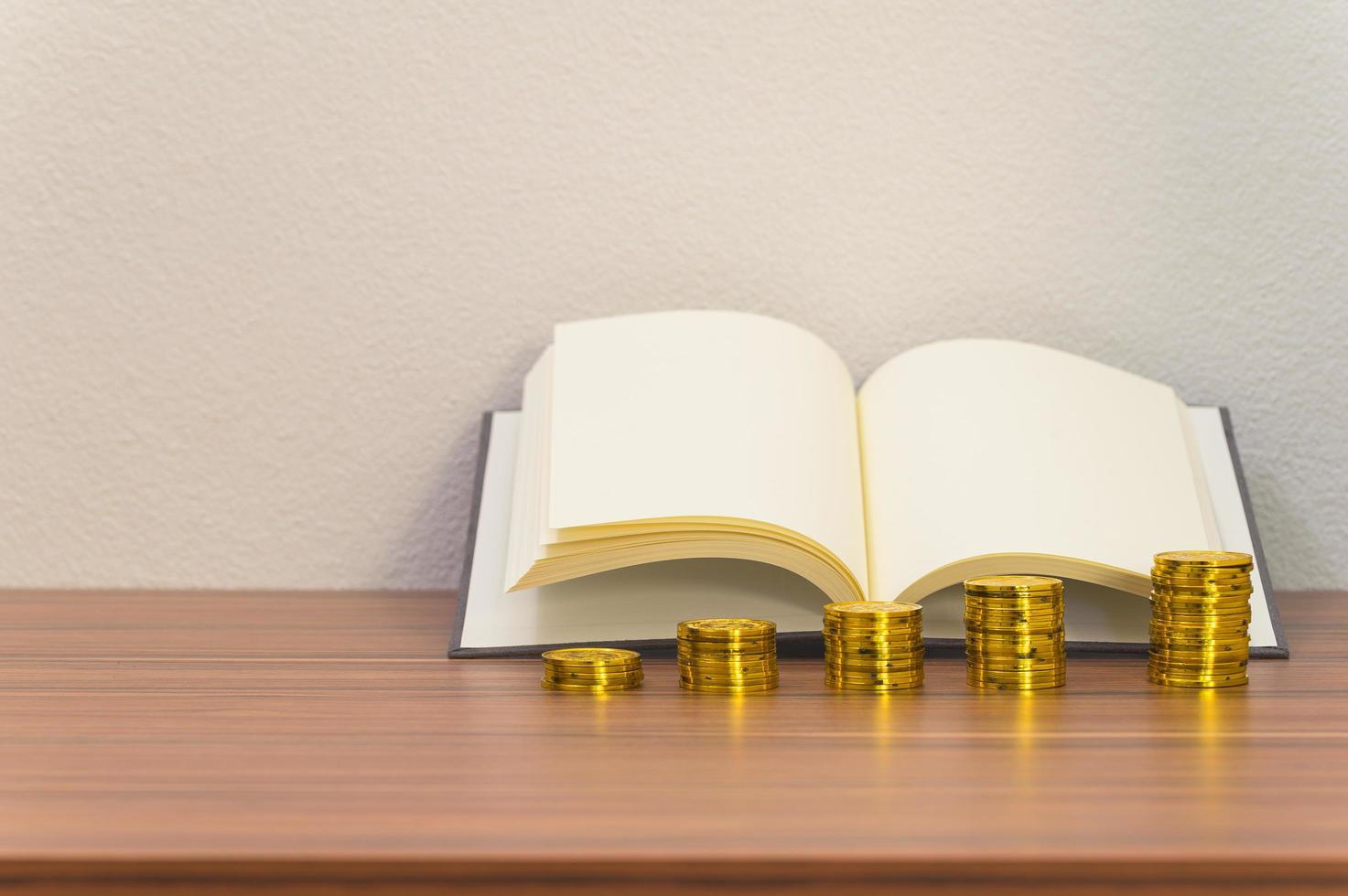 pilas de libros y monedas en el escritorio foto