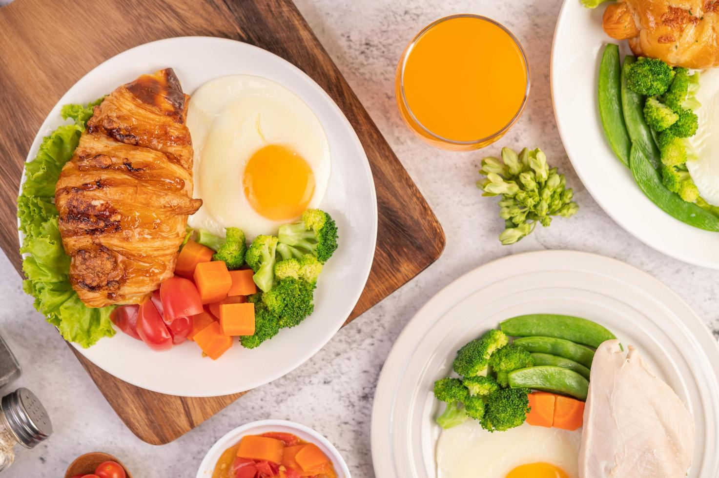 Breakfast spread of chicken, fried eggs, broccoli, carrots, tomatoes and lettuce photo