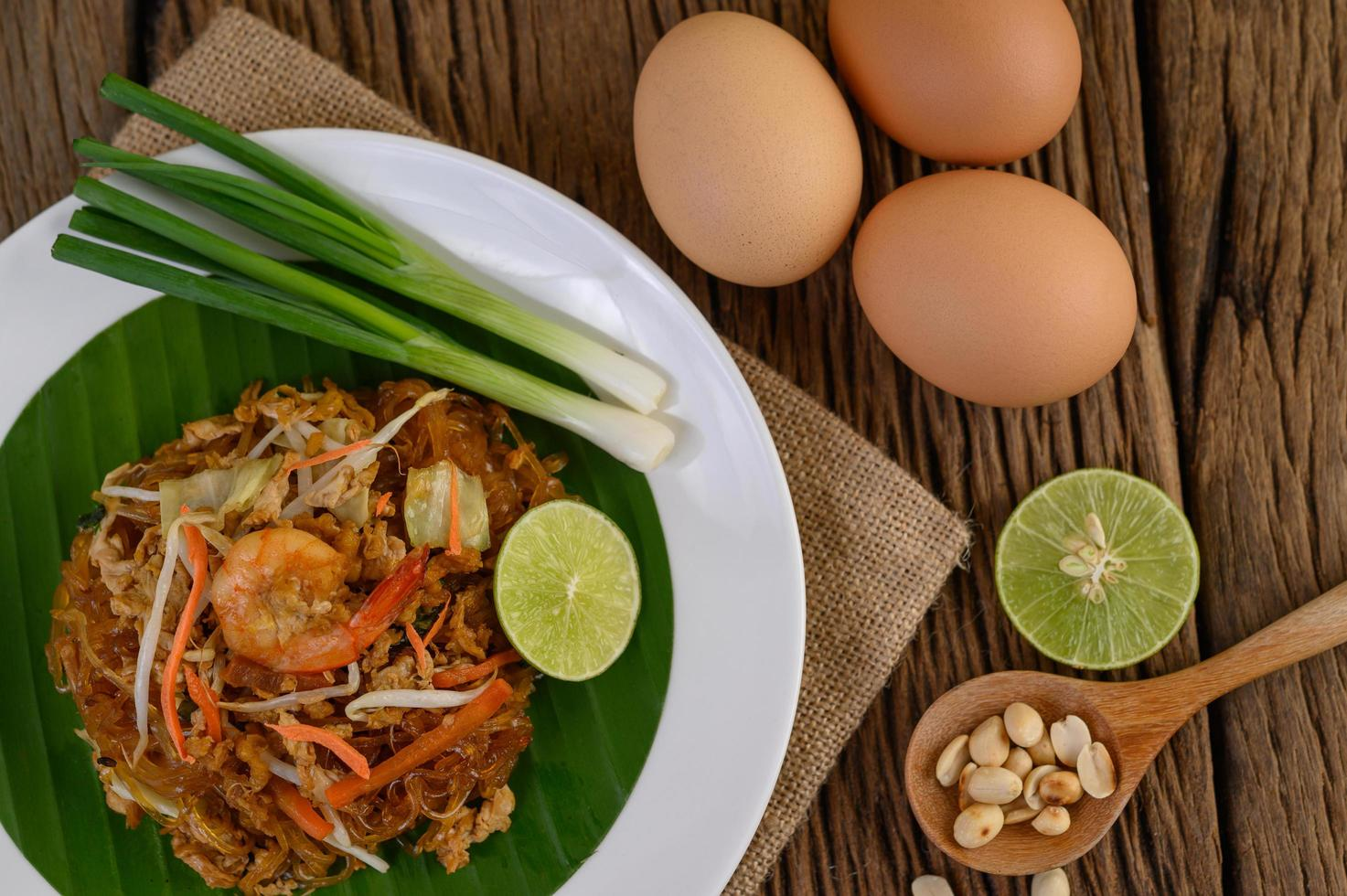 pad thai camarones en un bol con huevos, cebolleta y condimentos foto