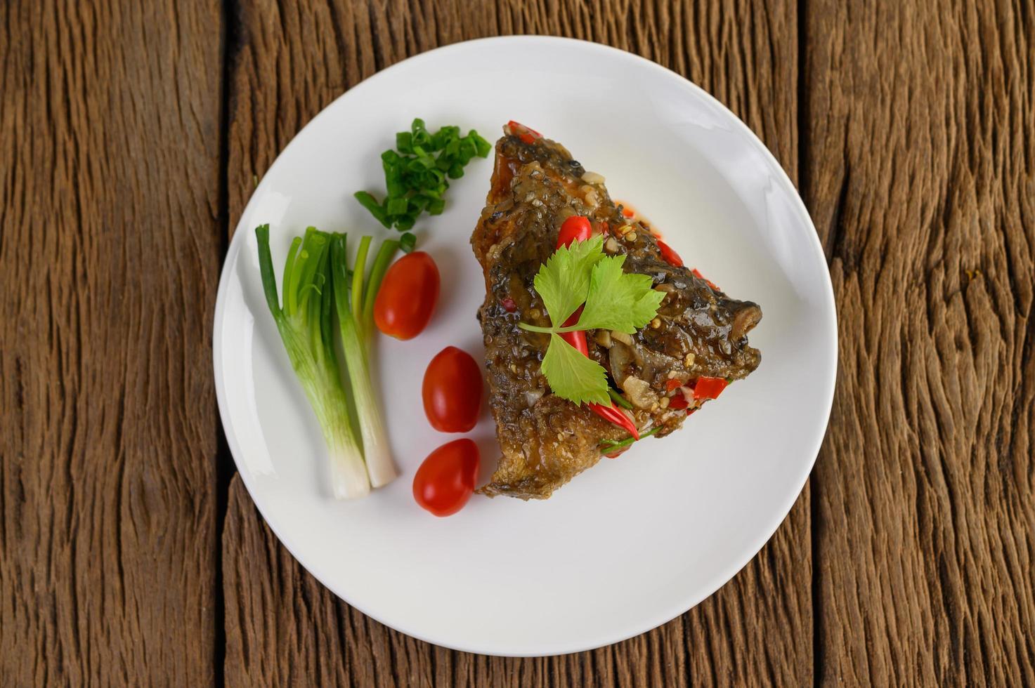 Cabeza de pescado frito cubierto con chiles en una placa blanca. foto