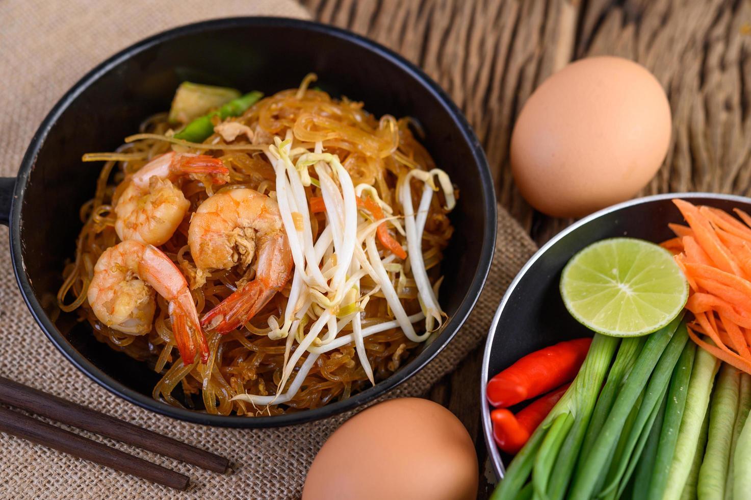pad thai camarones en una sartén negra con huevos y condimento foto