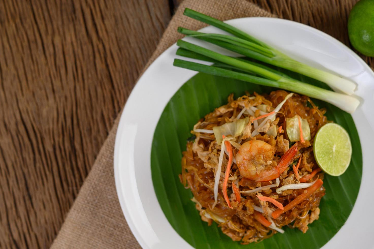 Plate of pad thai shrimp with lime and eggs photo