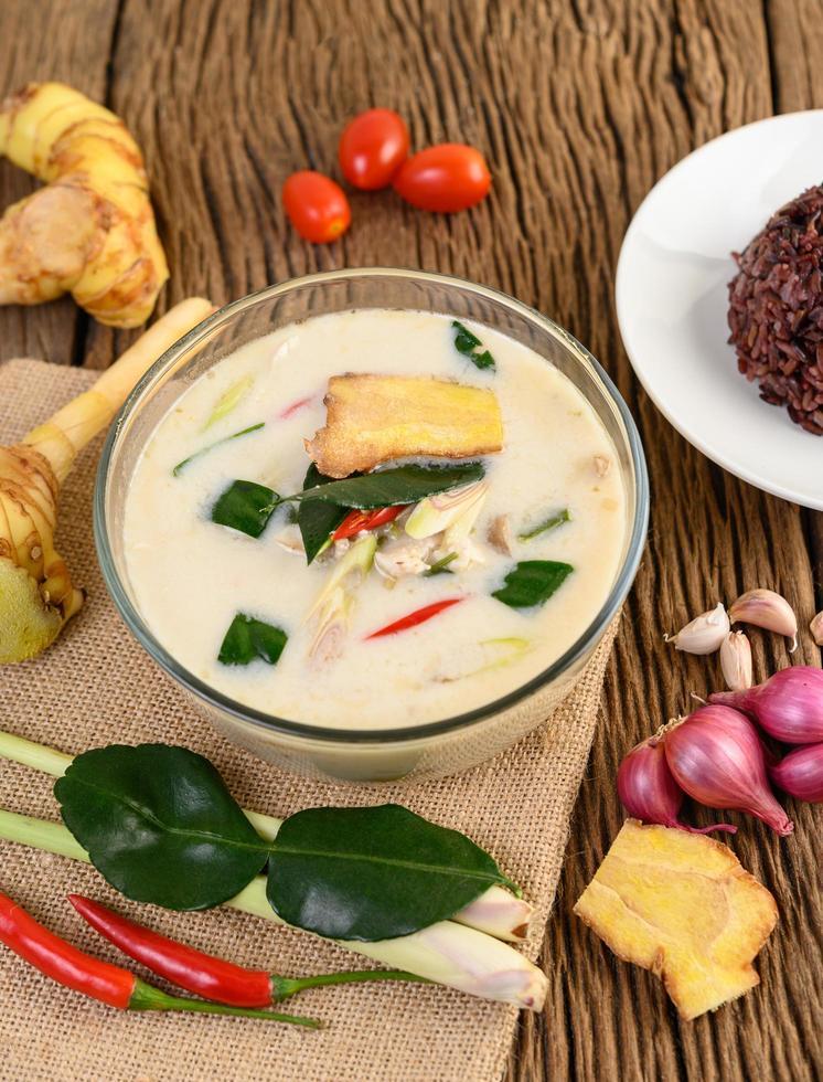 tom kha kai, sopa de coco tailandesa sobre tabla de cocina de madera foto