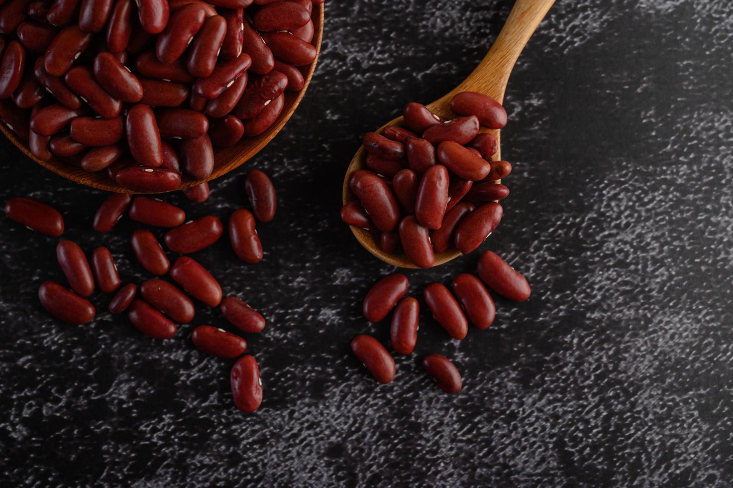 Frijoles rojos en tazones de madera sobre la superficie de la cocina negra foto