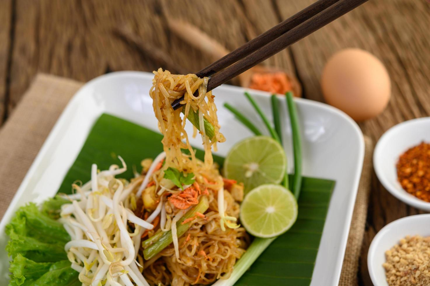 Pad Thai with lemon, eggs and seasoning on a wooden table photo