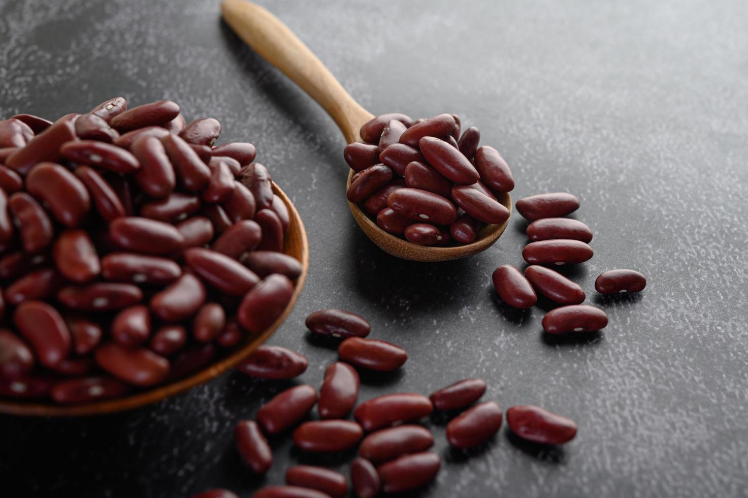 Red beans in wooden bowls on black kitchen surface photo