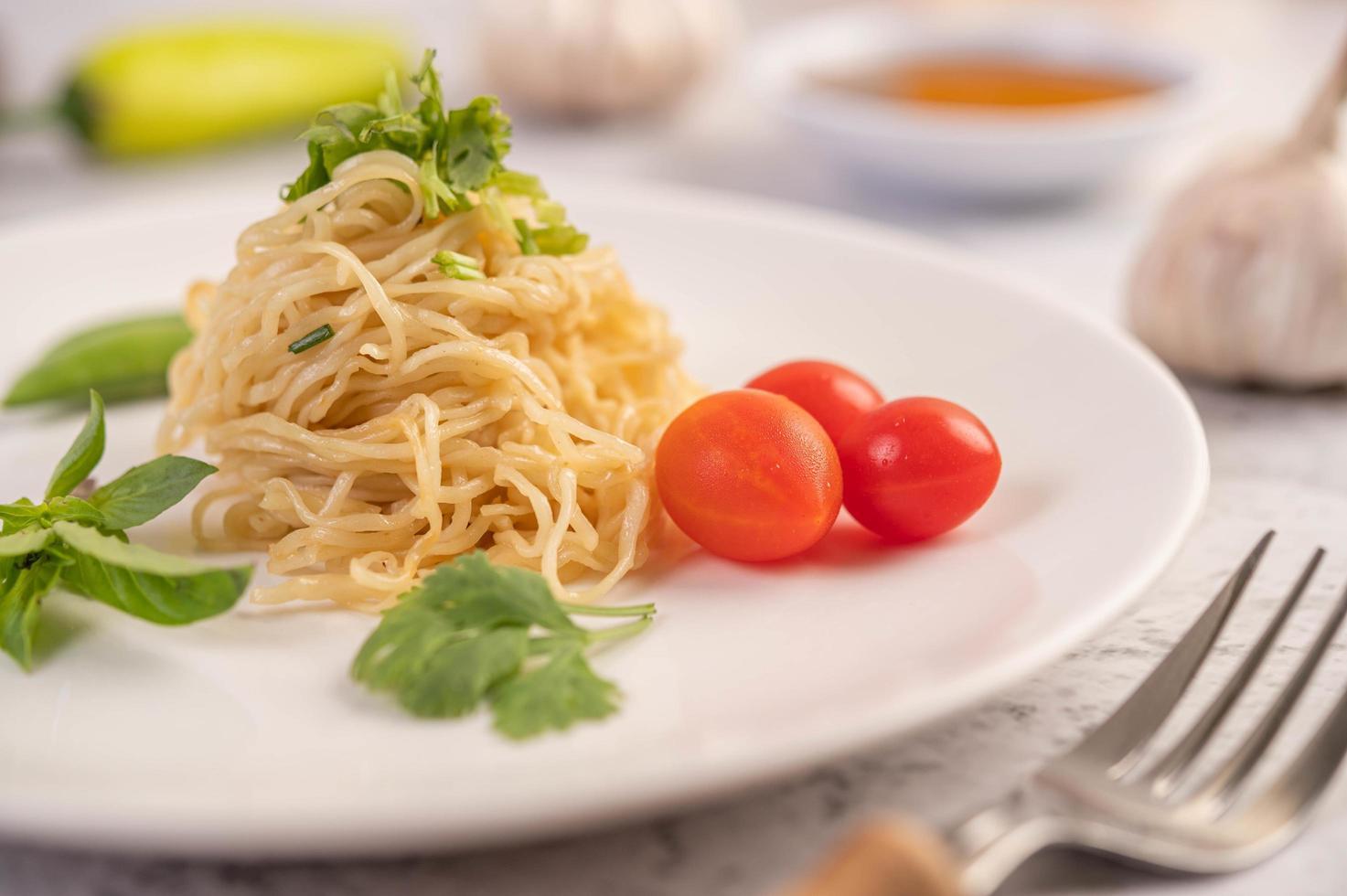 Spaghetti with tomatoes, coriander and basil photo