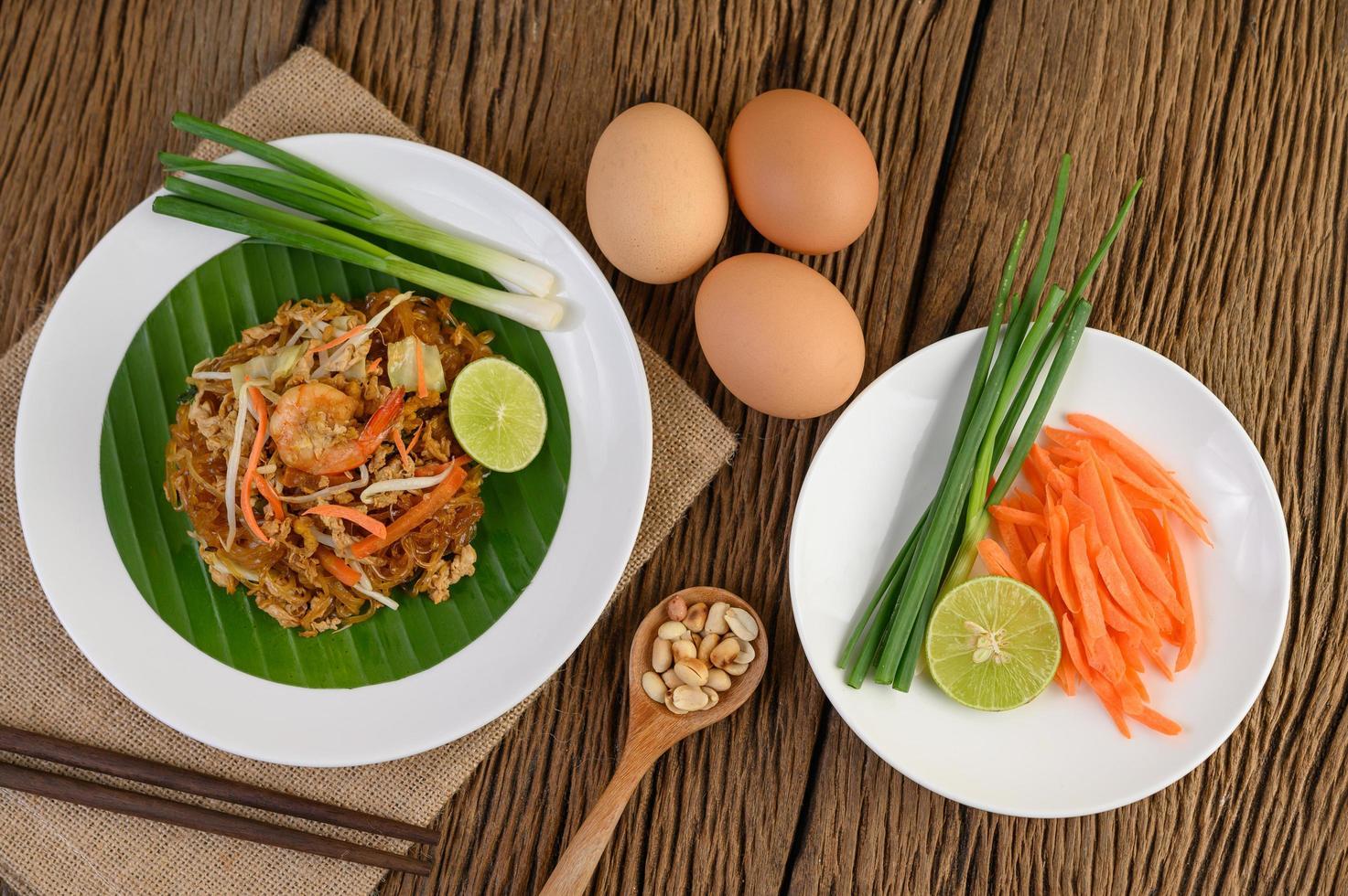 plato de pad thai camarones con limón y huevos foto