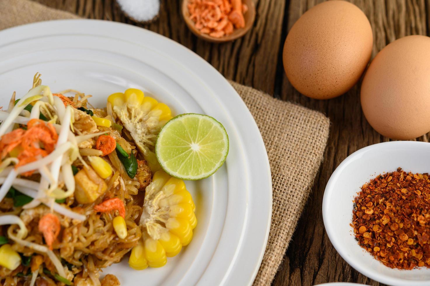 Pad thai con limón, huevos y condimentos sobre una mesa de madera foto