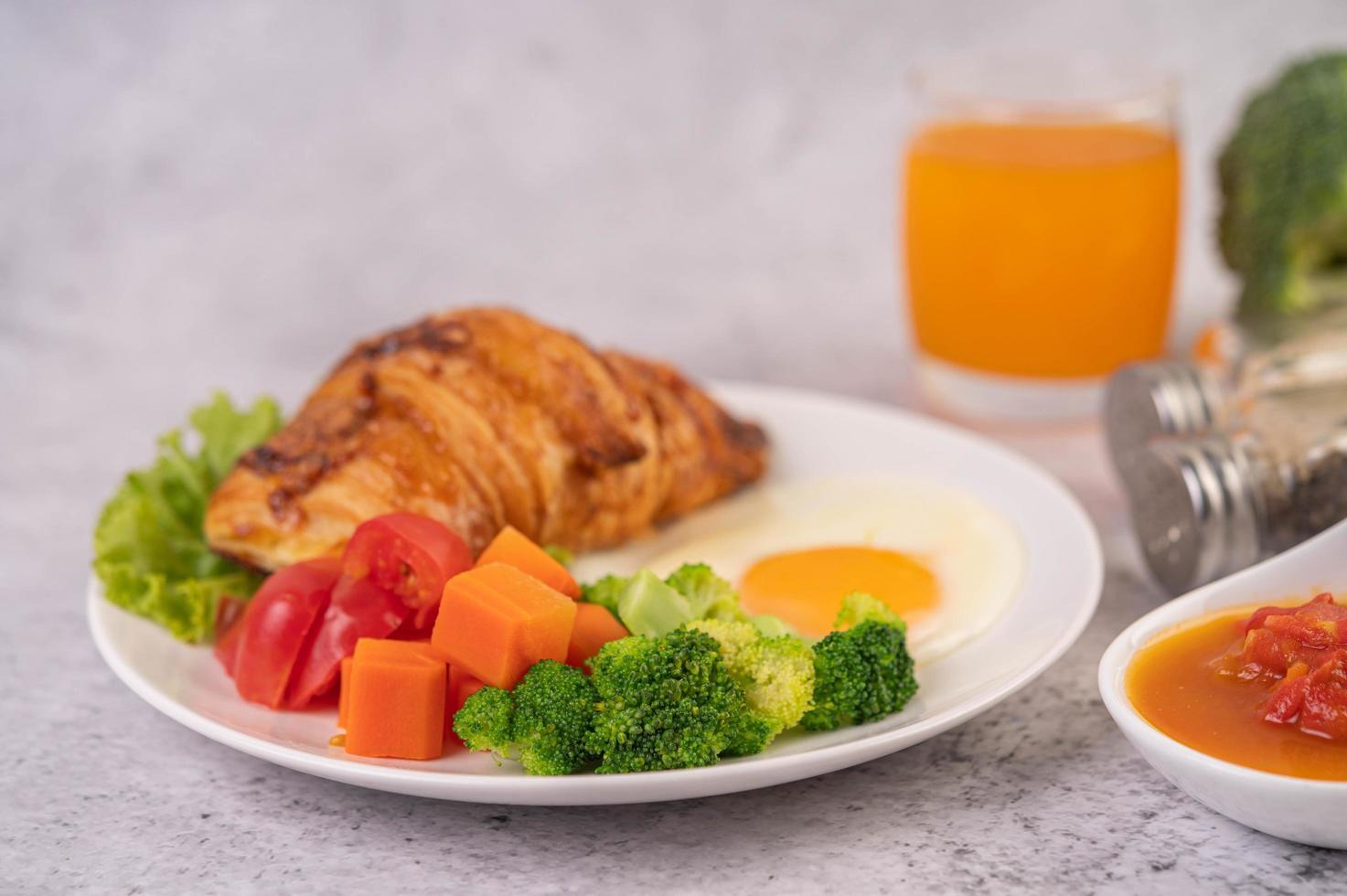 Fresh egg croissant and vegetable breakfast photo
