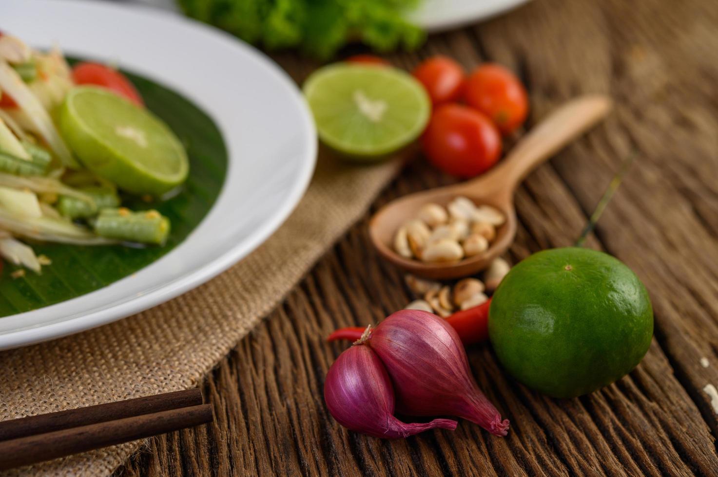 comida picante estilo tailandés con ajo, limón, cacahuetes, tomates y chalotas foto