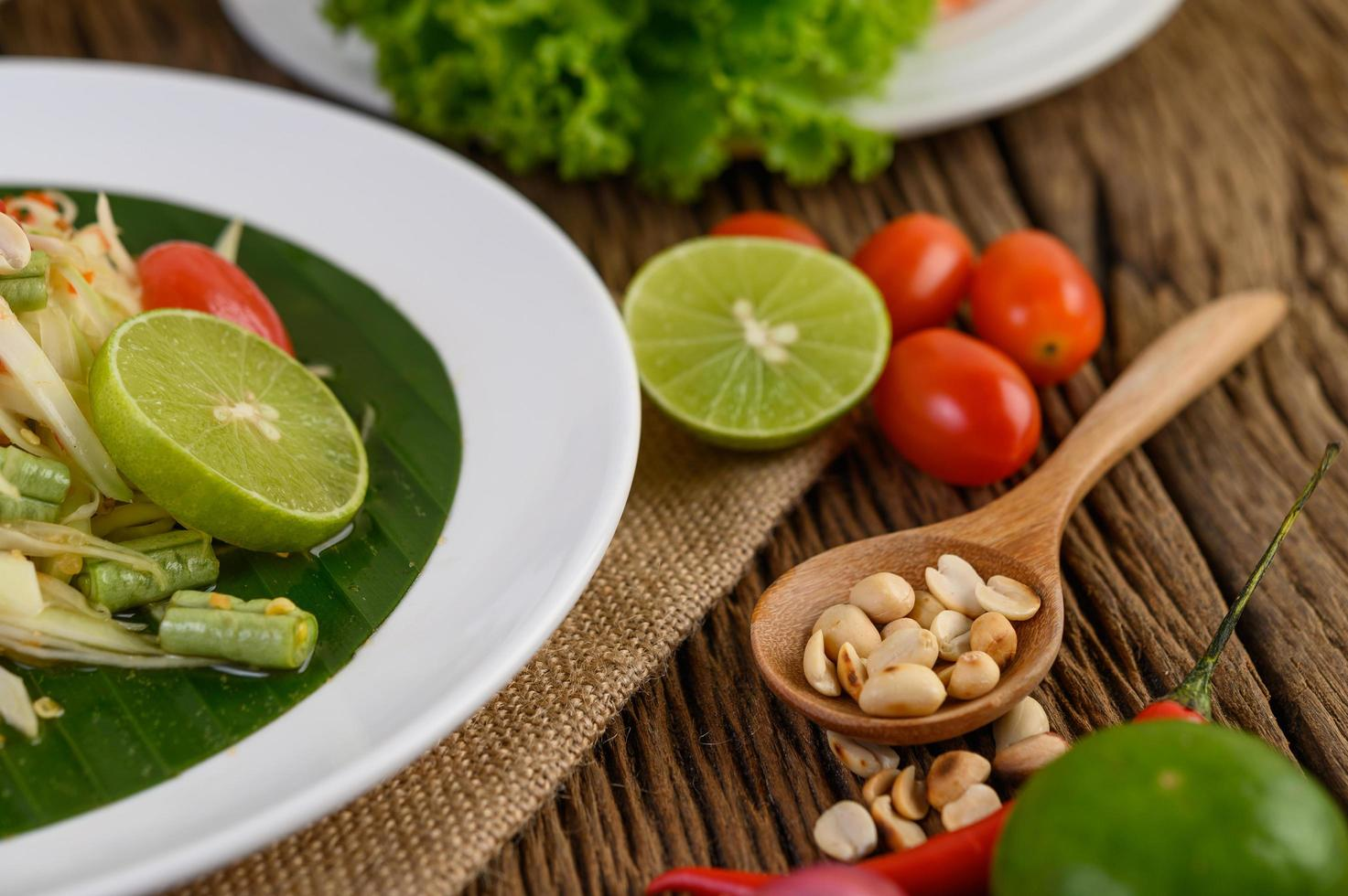 Thai style spicy food with garlic, lemon, peanuts, tomatoes, and shallots photo