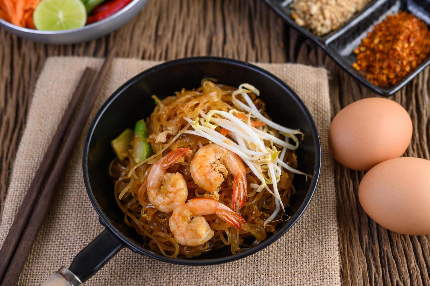 Pad thai shrimp in a black pan with eggs and seasoning photo