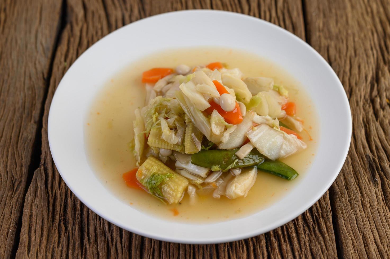Saltear las verduras mixtas en una placa blanca. foto