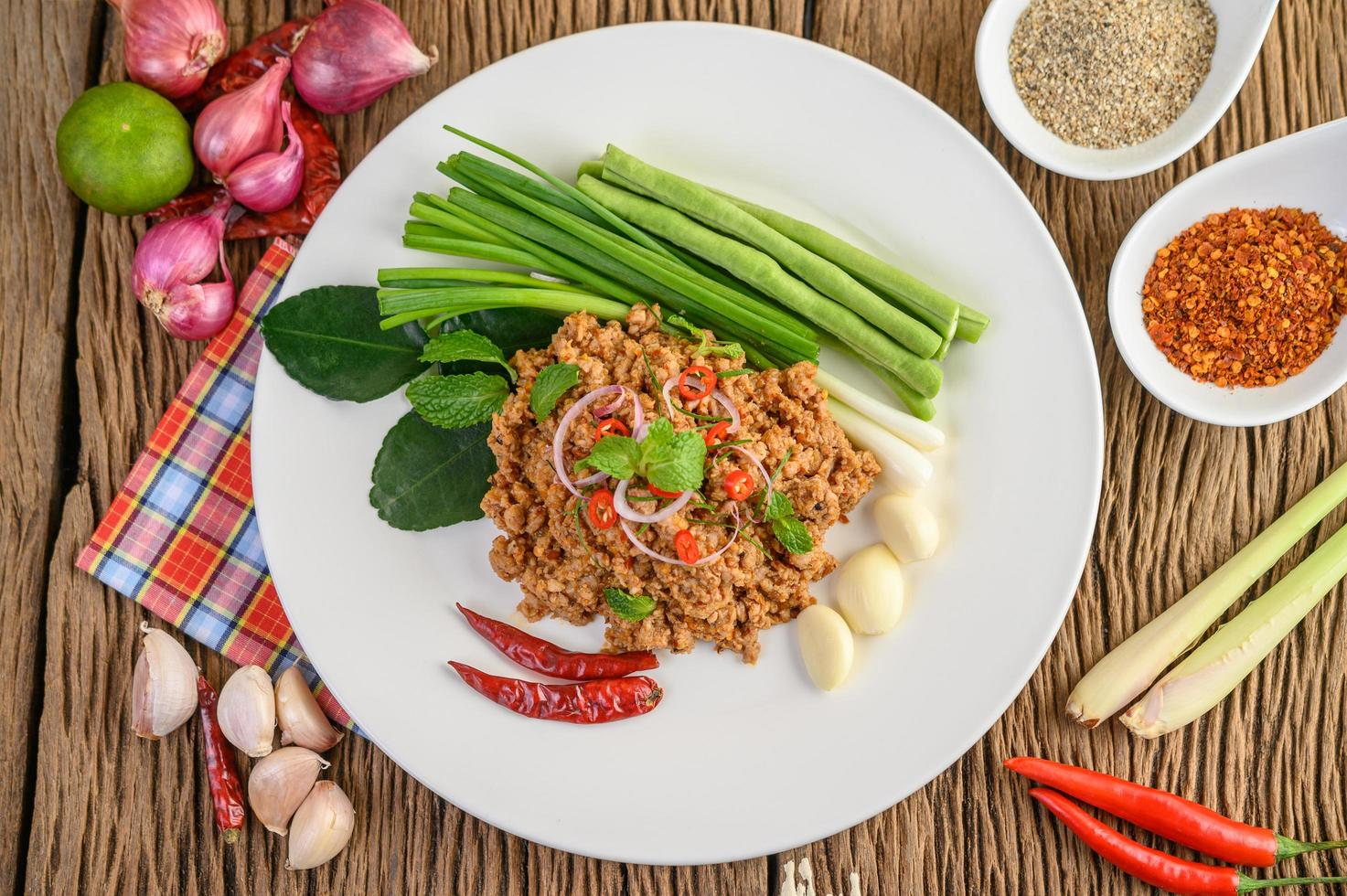 Minced pork salad with spices on a wooden table photo