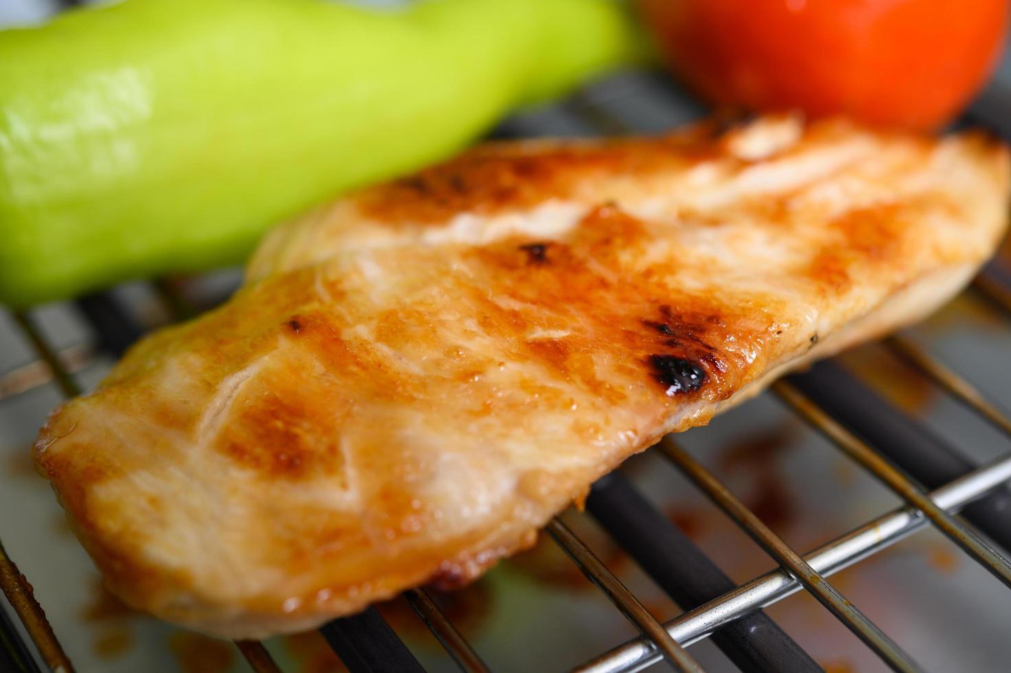 Pechuga de pollo a la plancha sobre una parrilla eléctrica con pimentón y tomate foto