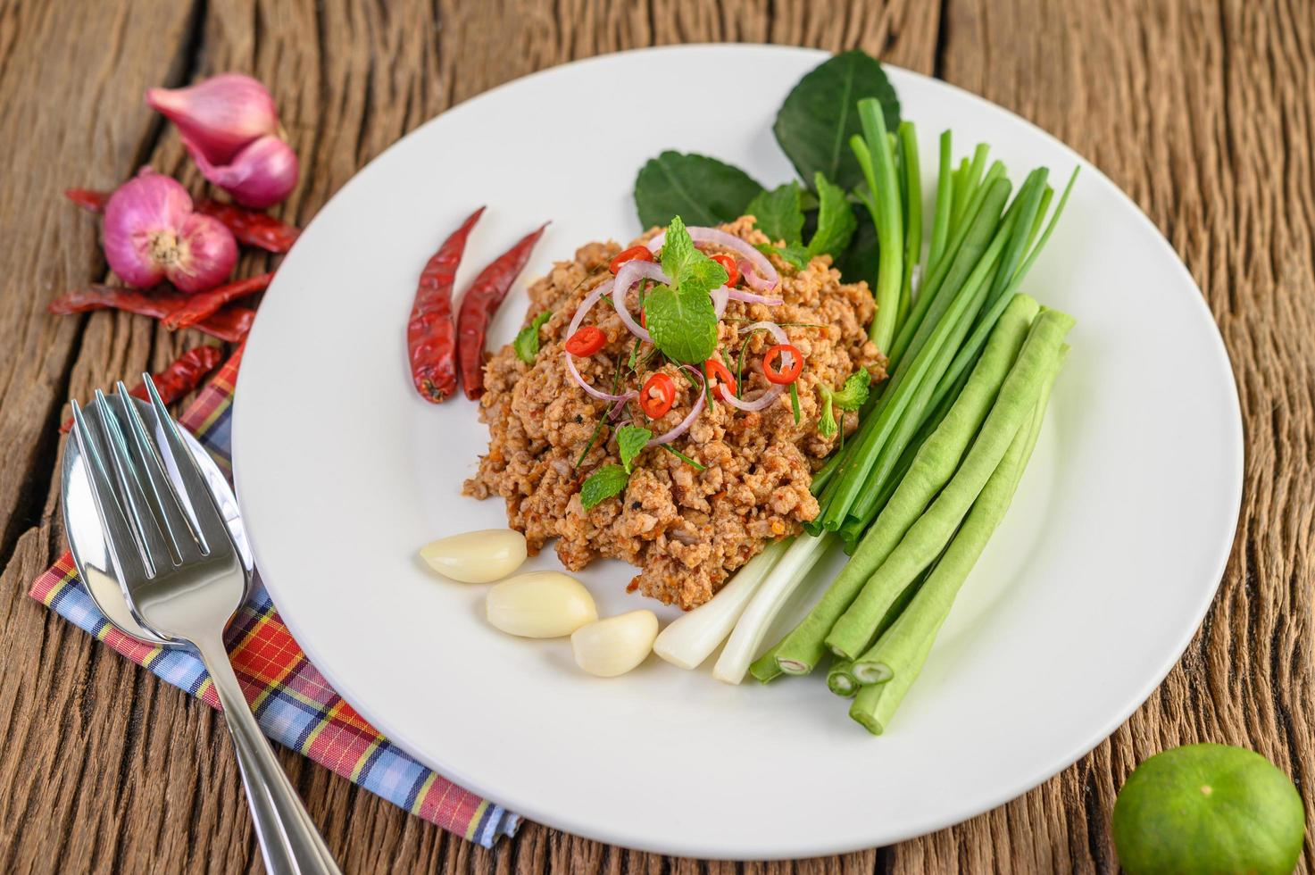 Spicy minced pork salad on green vegetables photo