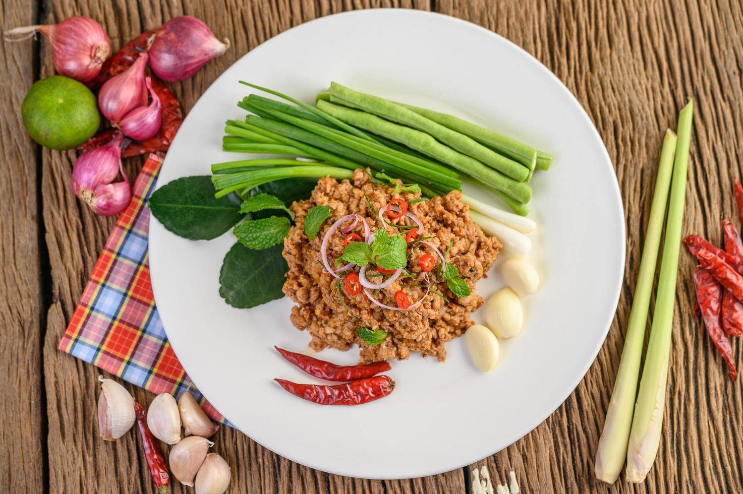 Ensalada picante de cerdo picada sobre verduras foto
