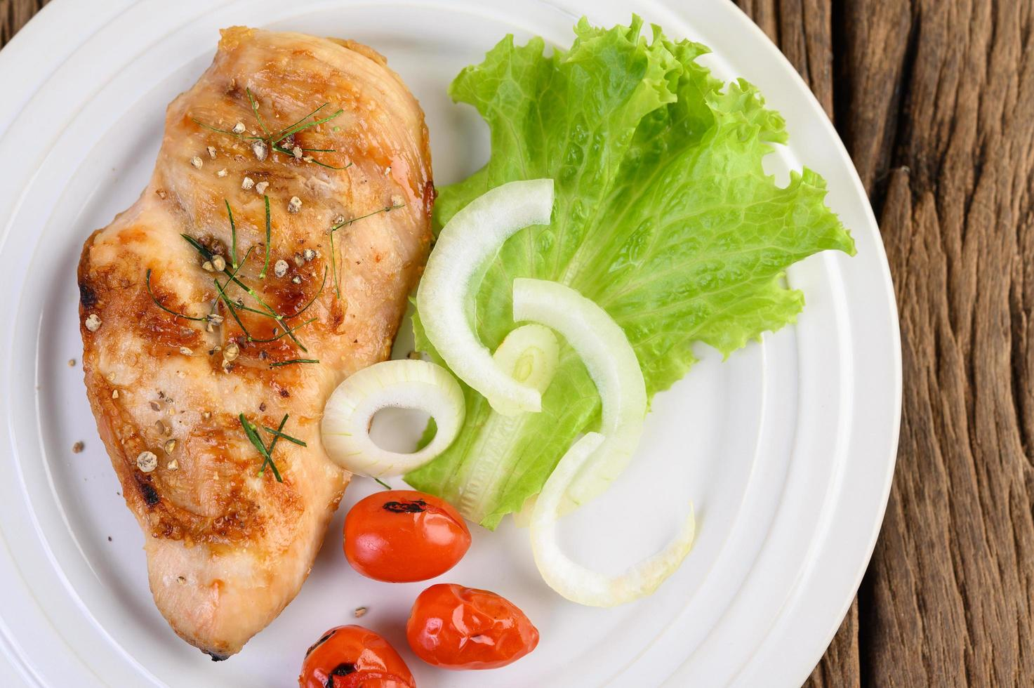 Grilled chicken on a plate with tomatoes, salad and onion photo