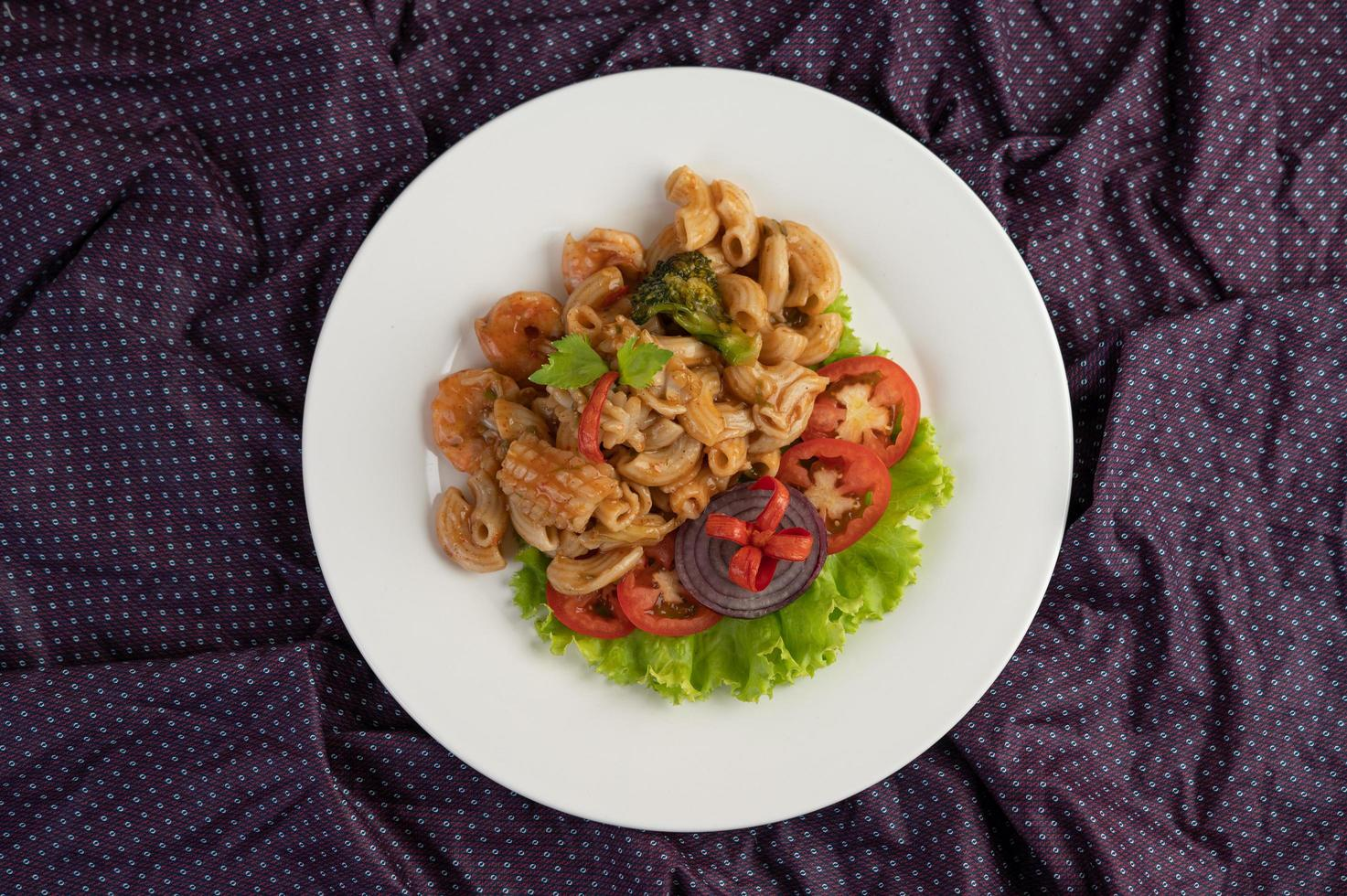 Stirred shrimp macaroni on a white plate with tomatoes and salad photo