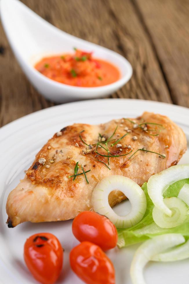 Grilled chicken on a wooden table with tomatoes, salad, onion and chili sauce photo