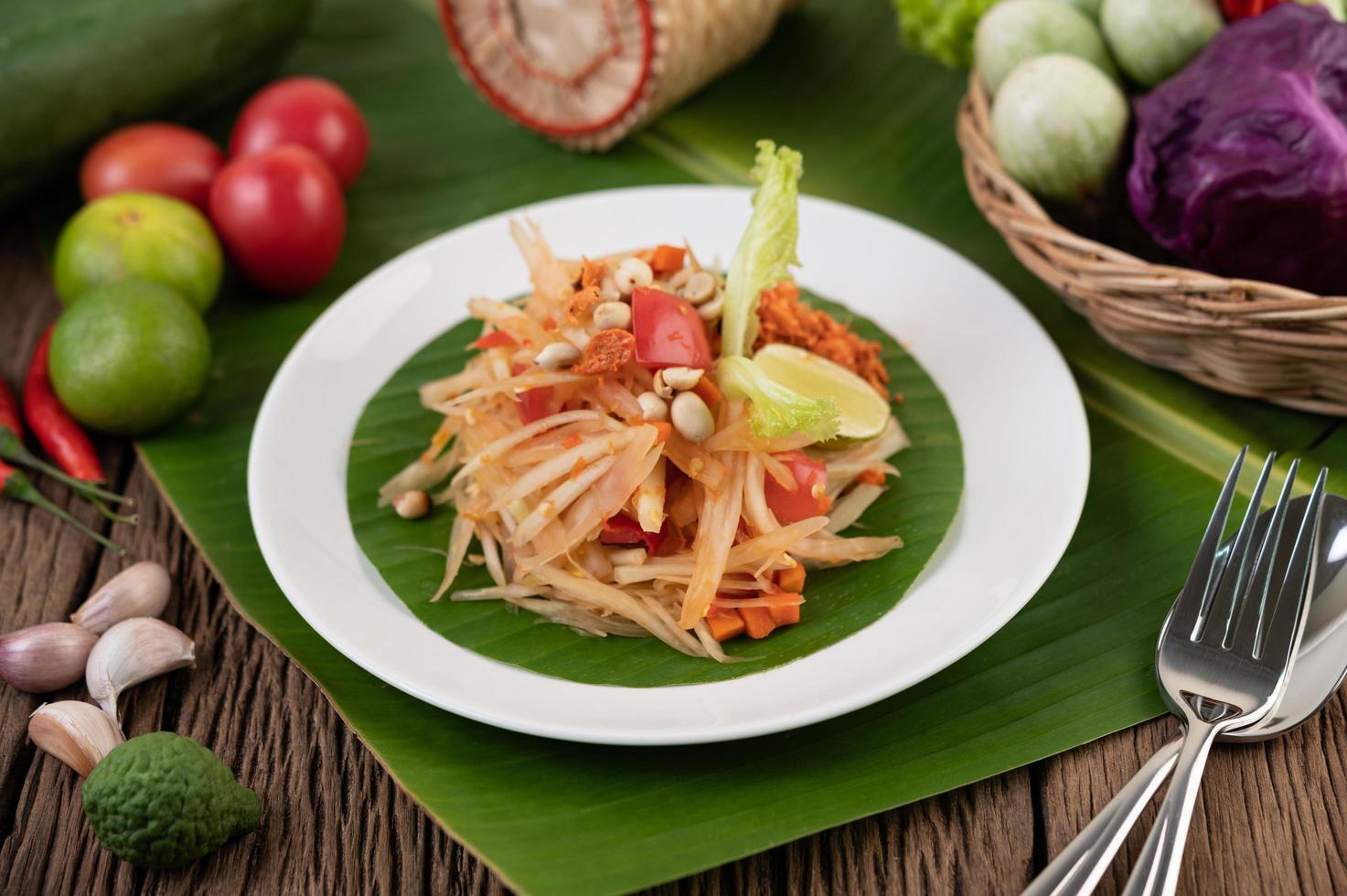 Thai papaya salad with banana leaves and fresh ingredients photo