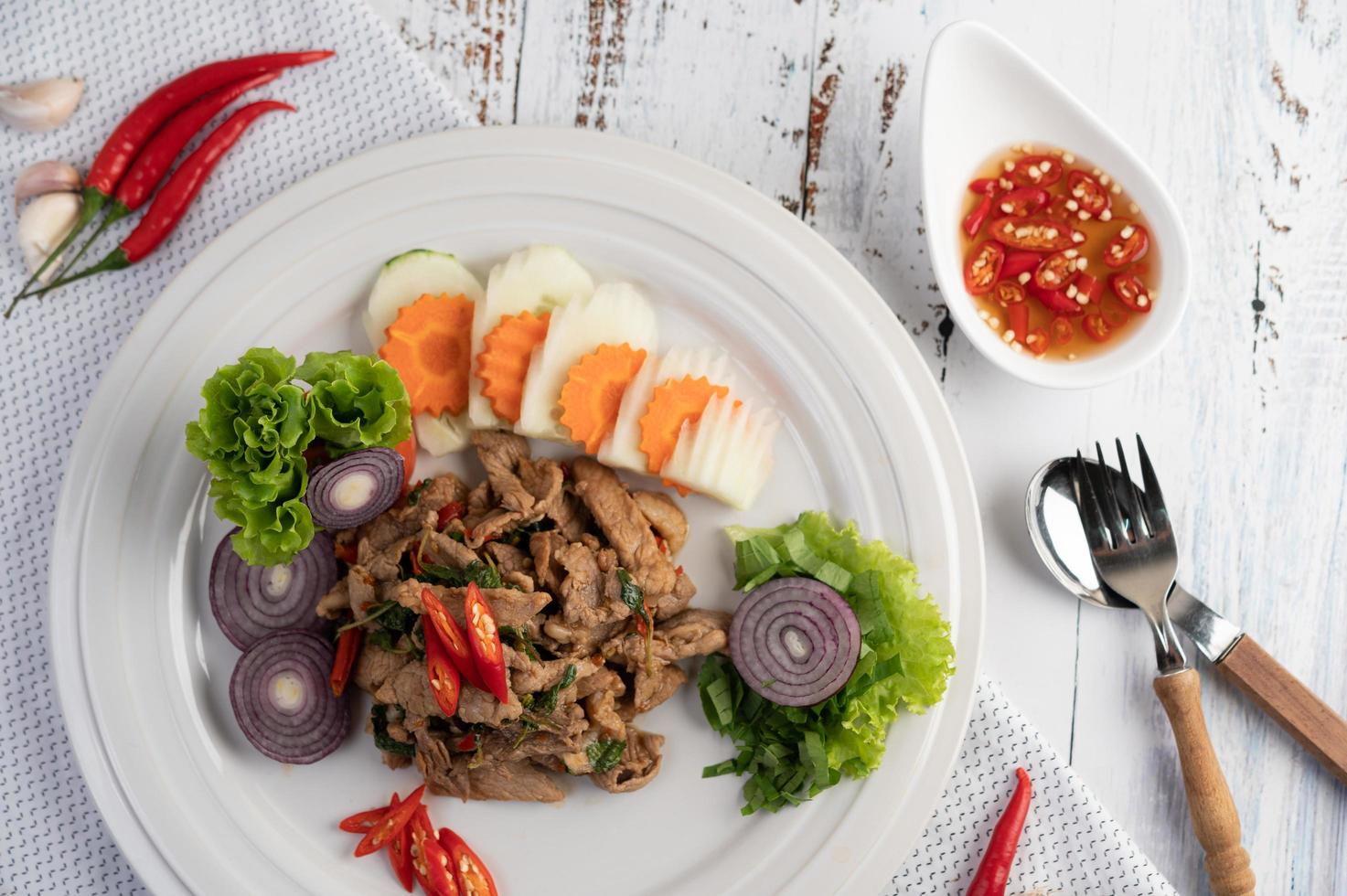 Stir-fried pork basil with carrots, cucumber and onion photo