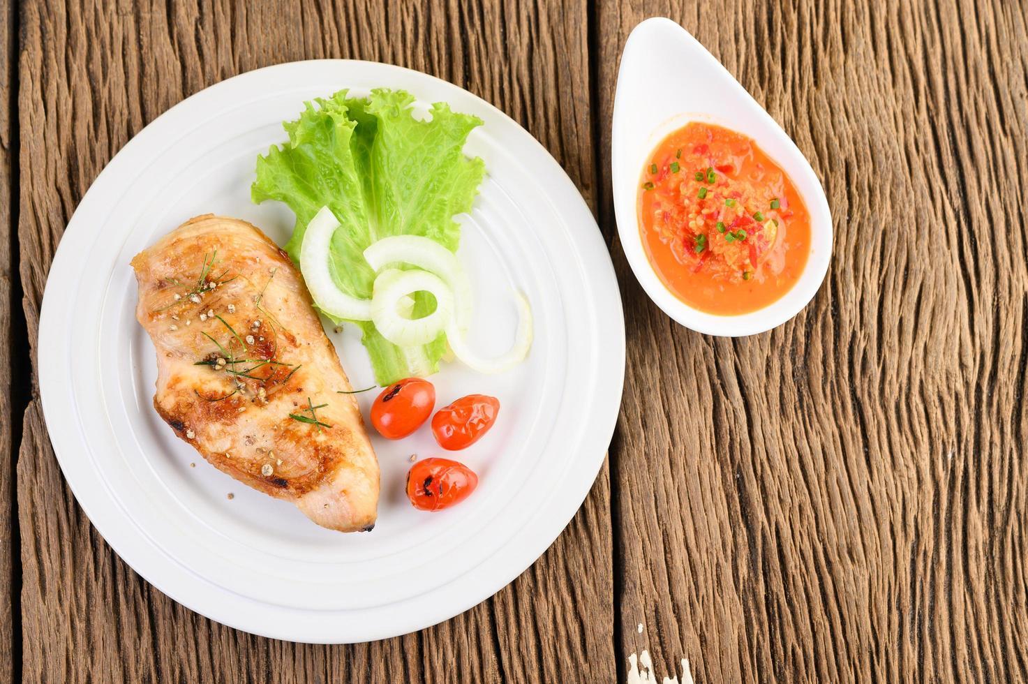 Pollo a la parrilla sobre una mesa de madera con tomate, ensalada, cebolla y salsa de chile foto