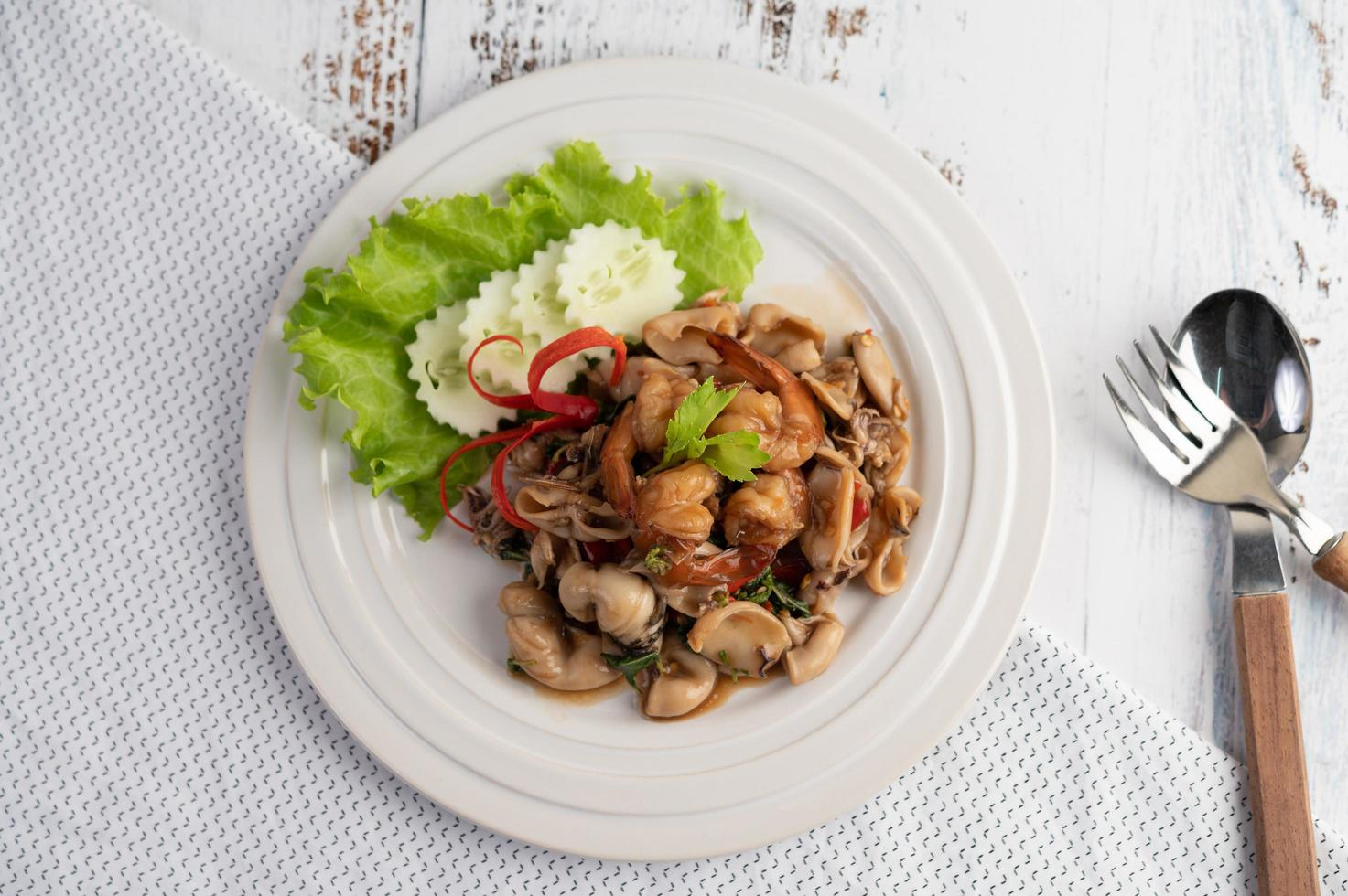 Plated and stir fried basil with squid and shrimp photo